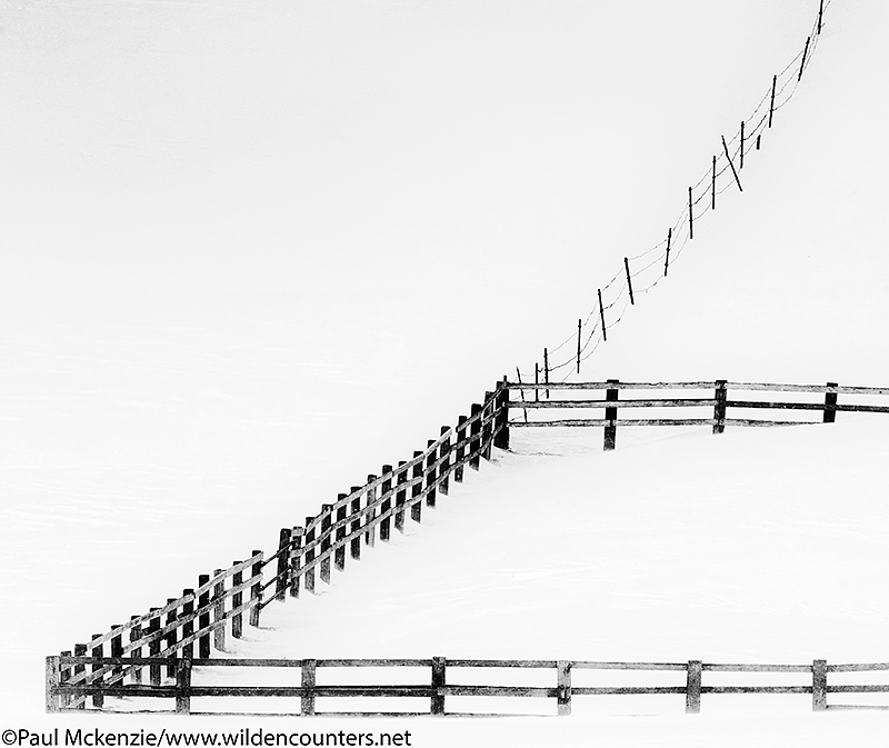 Fence on sloping snow-covered field, Eastern Hokkaido, Japan